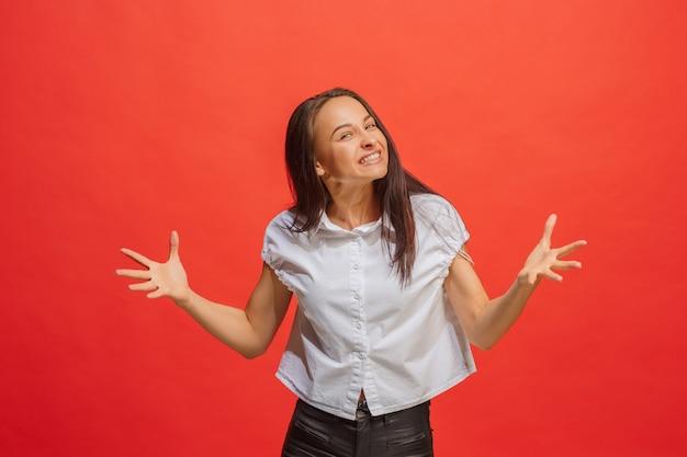 Mooi vrouwelijk half lengteportret dat op rode studio backgroud wordt geïsoleerd. de jonge emotionele verrast vrouw