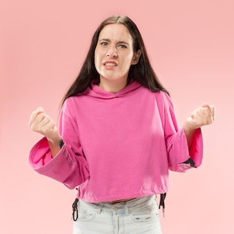 Mooi vrouwelijk half-lengteportret dat op roze studio wordt geïsoleerd