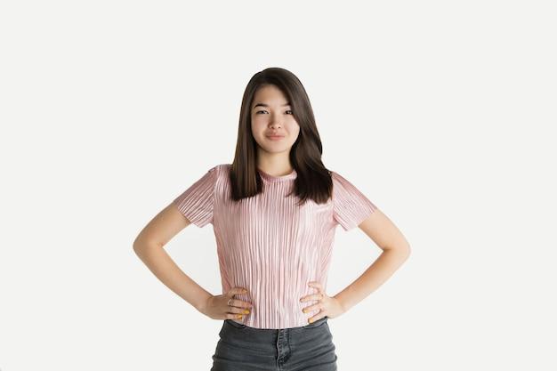 Mooi vrouwelijk half-lengteportret dat op witte ruimte wordt geïsoleerd. jonge emotionele vrouw in vrijetijdskleding. menselijke emoties, gezichtsuitdrukking concept