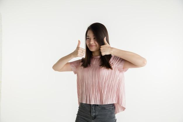 Mooi vrouwelijk half-lengteportret dat op witte ruimte wordt geïsoleerd. jonge emotionele vrouw in vrijetijdskleding