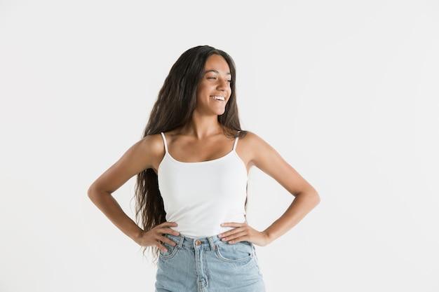 Mooi vrouwelijk half-lengteportret dat op witte studioachtergrond wordt geïsoleerd. jonge emotionele afro-amerikaanse vrouw met lang haar. gelaatsuitdrukking, concept van menselijke emoties. staan en glimlachen.