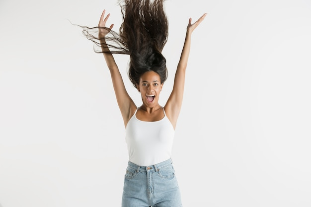 Mooi vrouwelijk half-lengteportret dat op witte studioachtergrond wordt geïsoleerd. jonge emotionele afro-amerikaanse vrouw met lang haar. gelaatsuitdrukking, concept van menselijke emoties. voelt zich gek gelukkig, springend.