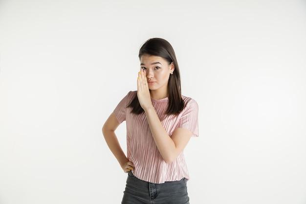 Mooi vrouwelijk half-lengteportret dat op witte studioachtergrond wordt geïsoleerd. jonge emotionele vrouw in vrijetijdskleding. menselijke emoties, gezichtsuitdrukking concept. een geheim fluisteren, verkoop.