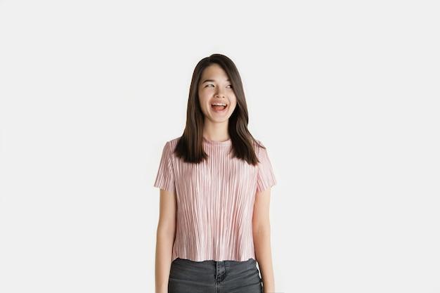 Mooi vrouwelijk half-lengteportret dat op witte studioachtergrond wordt geïsoleerd. jonge emotionele vrouw in vrijetijdskleding. menselijke emoties, gezichtsuitdrukking concept. gek blij, schreeuwend, lachend.