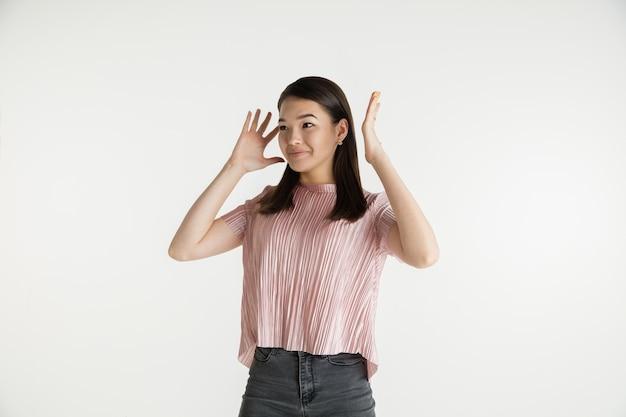 Mooi vrouwelijk half-lengteportret dat op witte studioachtergrond wordt geïsoleerd. jonge emotionele vrouw in vrijetijdskleding. menselijke emoties, gezichtsuitdrukking concept. geschokt, verbaasd, verwonderd.