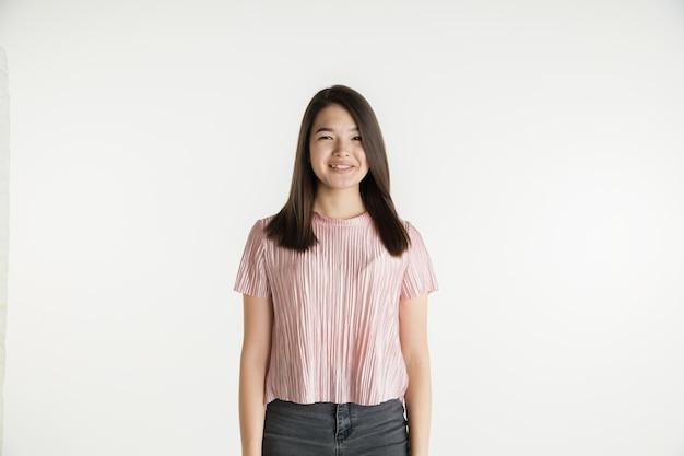 Mooi vrouwelijk half-lengteportret dat op witte studioachtergrond wordt geïsoleerd. jonge emotionele vrouw in vrijetijdskleding. menselijke emoties, gezichtsuitdrukking concept. glimlachend, ziet er zelfverzekerd uit.