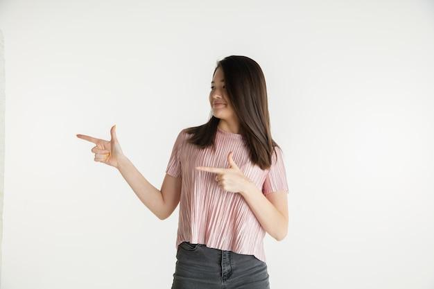 Mooi vrouwelijk half-lengteportret dat op witte studioachtergrond wordt geïsoleerd. jonge emotionele vrouw in vrijetijdskleding. menselijke emoties, gezichtsuitdrukking concept. naar opzij wijzend, glimlachend.