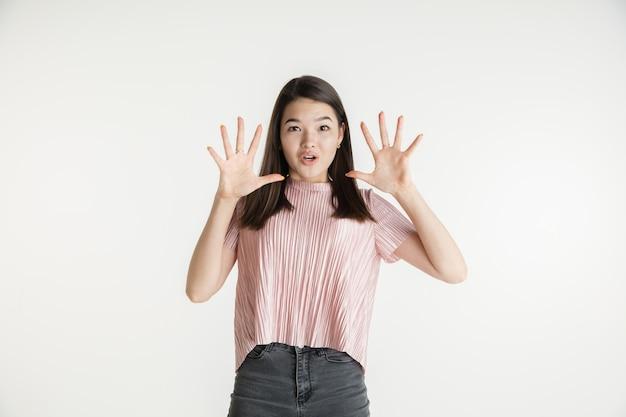 Mooi vrouwelijk half-lengteportret dat op witte studioachtergrond wordt geïsoleerd. jonge emotionele vrouw in vrijetijdskleding. menselijke emoties, gezichtsuitdrukking concept. verbaasd, vroeg zich af, belde om verkoop.