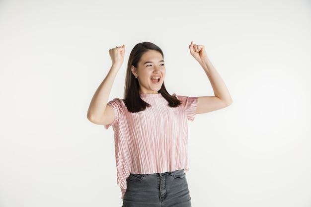 Mooi vrouwelijk half-lengteportret dat op witte studioachtergrond wordt geïsoleerd. jonge emotionele vrouw in vrijetijdskleding. menselijke emoties, gezichtsuitdrukking concept. vieren als winnaar, ziet er gelukkig uit.