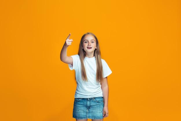 Mooi vrouwelijk half-length portret op oranje studio backgroud. het jonge emotionele tienermeisje