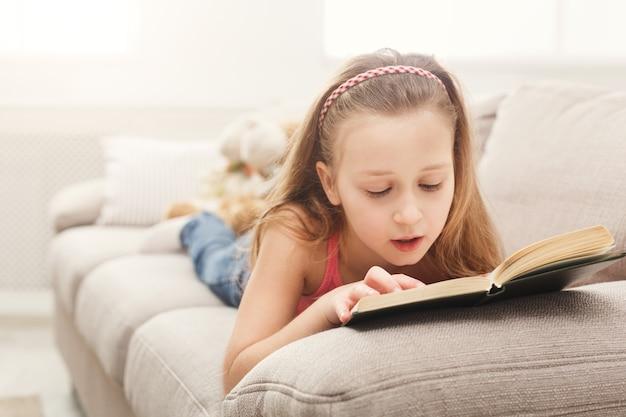 Mooi vrouwelijk kind dat een boek leest dat thuis op de bank ligt