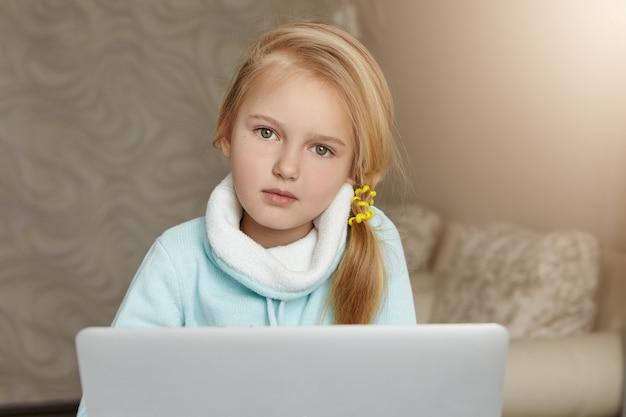 Mooi vrouwelijk kind met blonde haren, surfen op internet op haar laptopcomputer