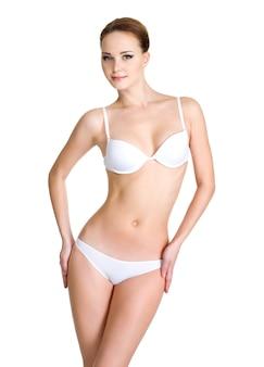 Mooi vrouwelijk lichaam in wit ondergoed dat op wit wordt geïsoleerd
