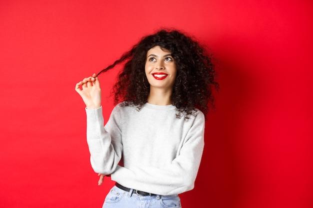 Mooi vrouwelijk model dat met krullen speelt en gelukkig omhoog kijkt, dromerig over iets denkt, staande tegen een rode achtergrond