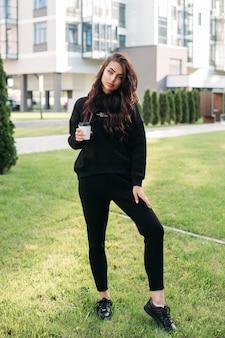 Mooi vrouwelijk model met krullend haar, gekleed in stijlvol zwart trainingspak en kopje koffie. vrouwelijke mode. stadslevensstijl
