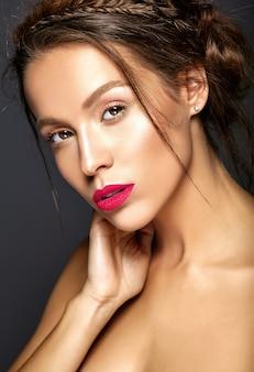 Mooi vrouwelijk model met verse dagelijkse make-up met rode lippen