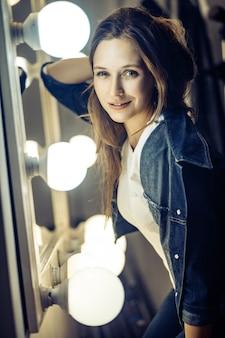 Mooi vrouwelijk model poseren in de buurt van spiegel