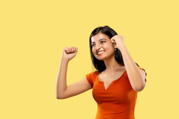 Mooi vrouwelijk portret van halve lengte dat op gele ruimte wordt geïsoleerd. jonge emotionele indiase vrouw die in jurk een overwinning viert. negatieve ruimte