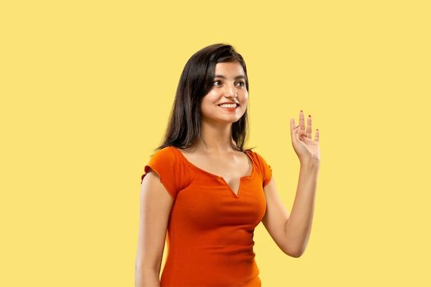 Mooi vrouwelijk portret van halve lengte dat op gele ruimte wordt geïsoleerd. jonge emotionele indiase vrouw in jurk groet en uitnodigend. negatieve ruimte