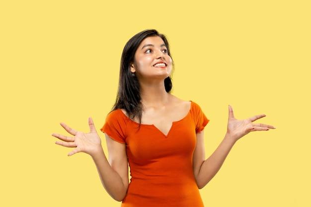 Mooi vrouwelijk portret van halve lengte dat op gele ruimte wordt geïsoleerd. jonge emotionele indiase vrouw in jurk verbaasd en blij. negatieve ruimte