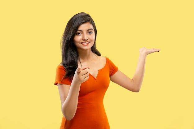 Mooi vrouwelijk portret van halve lengte dat op gele ruimte wordt geïsoleerd. jonge emotionele indiase vrouw in jurk wijzen en tonen. negatieve ruimte