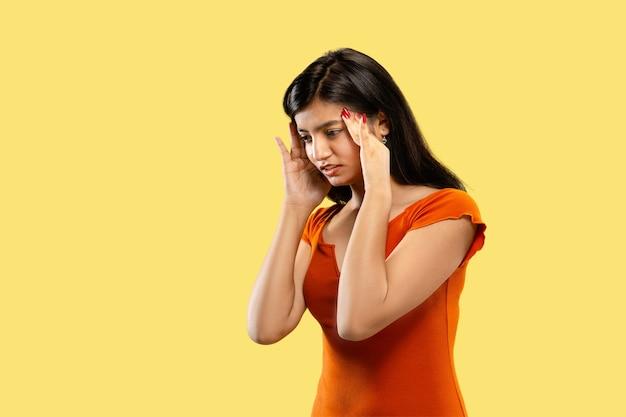 Mooi vrouwelijk portret van halve lengte dat op gele ruimte wordt geïsoleerd. jonge emotionele indiase vrouw in nadenkende jurk of lijdt aan de pijn