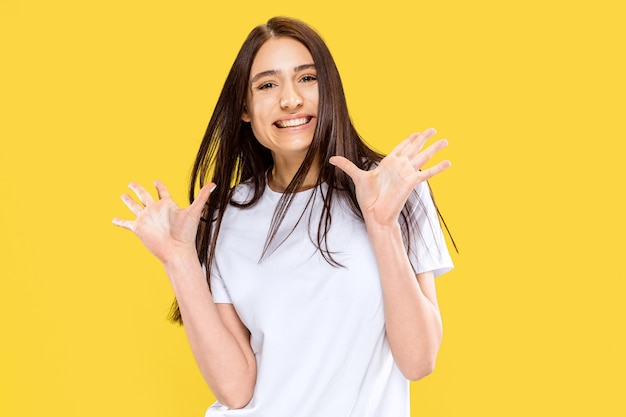 Mooi vrouwelijk portret van halve lengte dat op gele ruimte wordt geïsoleerd. jonge glimlachende vrouw. gelaatsuitdrukking, zomer, weekend, resortconcept