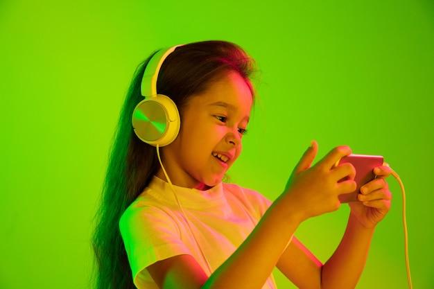 Mooi vrouwelijk portret van halve lengte dat op groene muur in neonlicht wordt geïsoleerd. jong emotioneel meisje. menselijke emoties, gezichtsuitdrukking concept. smartphone gebruiken voor vlog, selfie, chating, gaming.