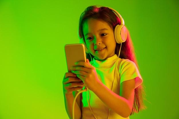 Mooi vrouwelijk portret van halve lengte dat op groene muur in neonlicht wordt geïsoleerd. jong emotioneel meisje.