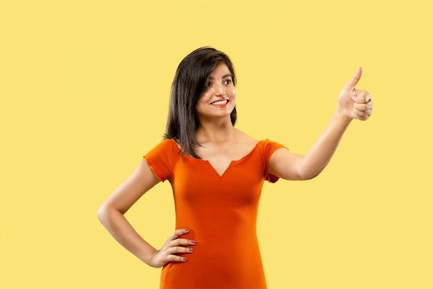 Mooi vrouwelijk portret van halve lengte op gele studio