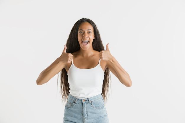 Mooi vrouwelijk portret van halve lengte op witte studioachtergrond. jonge emotionele afro-amerikaanse vrouw met lang haar. gelaatsuitdrukking, concept van menselijke emoties. teken van cool of geweldig laten zien.