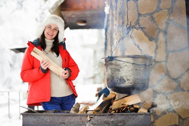 Mooi vrouwen kokend diner in de winter in openlucht.