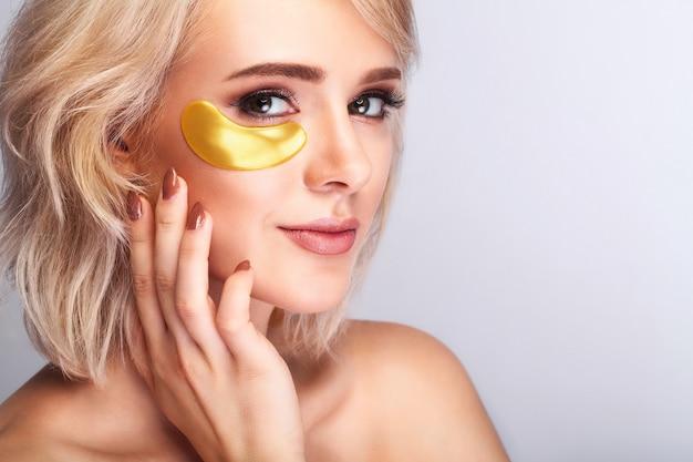 Mooi vrouwengezicht met gouden hydrogelpleisters, opheffend antirimpelcollageenmasker op verse gezonde gezichtshuid.