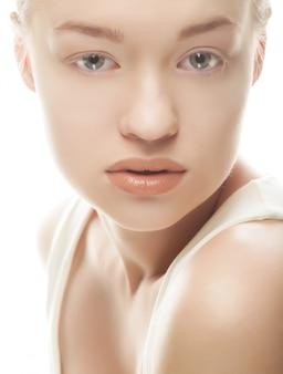 Mooi vrouwengezicht met schone huid - die op wit wordt geïsoleerd