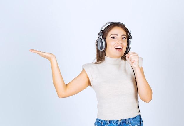 Mooi vrouwenmodel dat muziek in hoofdtelefoons luistert en zingt.