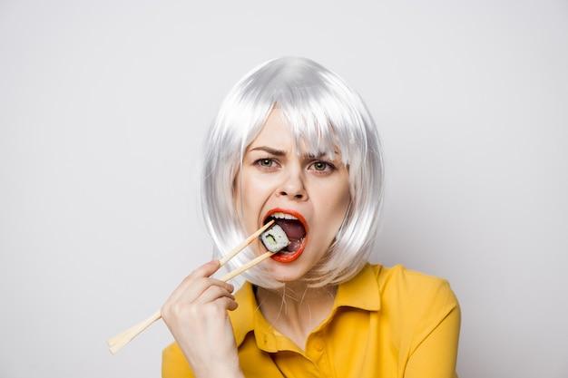Mooi vrouwenmodel dat sushi en broodjes van voedsellevering eet in een gele overhemdsemoties