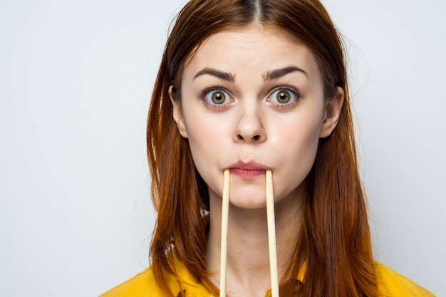 Mooi vrouwenmodel die sushi en broodjes van voedsellevering bij de lijst in een geel overhemd eten die verschillende emoties stellen