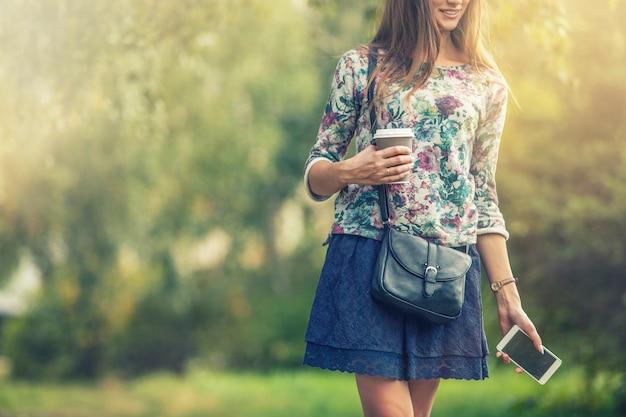 Mooi vrouwenmodel met afhaalkoffie en een telefoon in het park. stijl, casual, drankje, geluk, zonnig