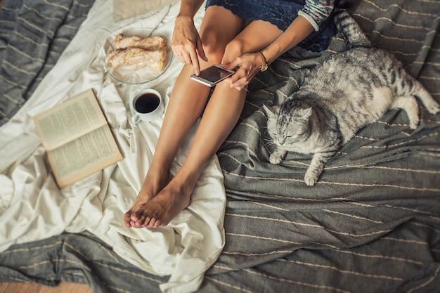 Mooi vrouwenmodel met koffie, gebak, huistelefoon op de deken met een kat. ontbijt, ochtend, thuis, comfort