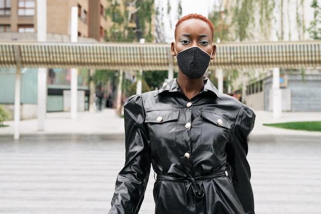 Mooi vrouwenmodel met masker vanwege coronavirus pandemie covid 19 wandelen in stijl op straat met een mooie zwarte jurk
