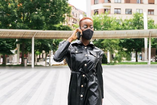 Mooi vrouwenmodel met masker vanwege de coronavirus-pandemie covid 19 praat op haar mobiele telefoon en zorgt voor haar zaken op straat
