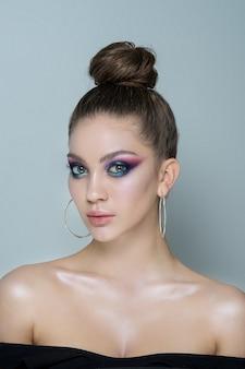 Mooi vrouwenmodel met professionele make-up in een zwarte avondjurk en grote oorbellen in haar oren