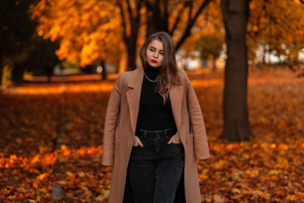 Mooi vrouwenmodel met rode lippen in een modieuze beige jas en trui loopt in het herfstpark met gekleurd oranje blad