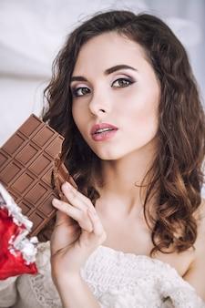 Mooi vrouwenmodel met tegels van donkere chocolade in handen tegen slaapkamerbinnenland
