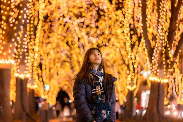 Mooi vrouwenportret in de winterkleding bij nacht in het jozenji-kerstmislicht op festival in sendai, japan