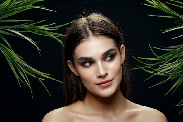 Mooi vrouwenportret in palmstruiken, mooie huid van het gezicht