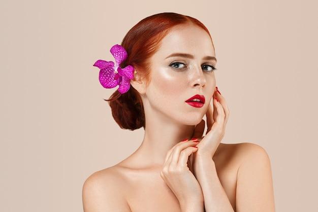 Mooi vrouwenportret met bloem in haar. perfecte make-up manicure rode lippen en nagels. beige achtergrond