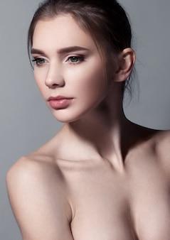 Mooi vrouwenportret met natuurlijke make-up op grijs