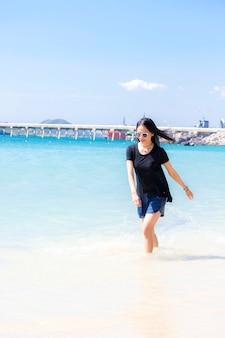 Mooi vrouwenportret op het strand. ze is blij en glimlacht. ziet er ontspannen uit en kan op vakantie zijn met de zon en de zee achter haar