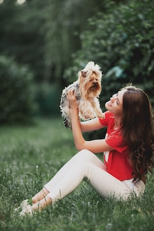 Mooi vrouwenspel met hond terwijl het zitten op gras in het groene park